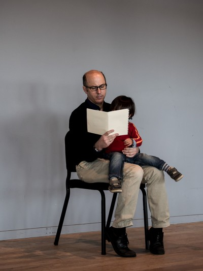 Composer Ned McGowen reads a score with his son sitting on his lap.